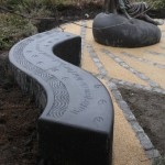 """View of the sculptural bench carrying the words """"Water from the West Port Well revived a wearie Drover Girl"""""""